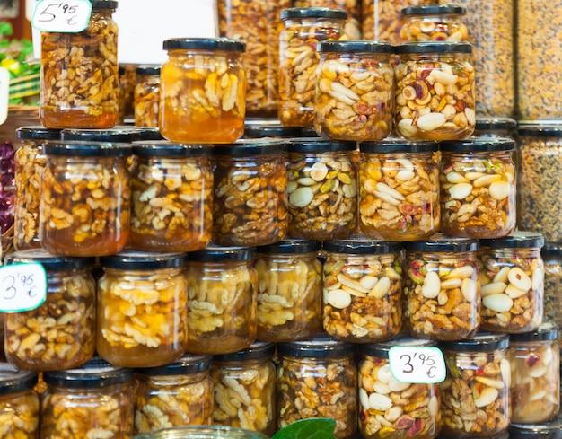 Miel d'abeille avec des noix dans des boîtes de verre