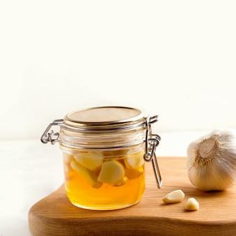 Miel à l'ail sur une plaque blanche à côté des ingrédients. espace de copie