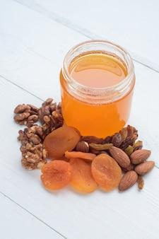 Miel, amandes, noix et abricots secs. fruits secs allongés sur une table en bois blanc.