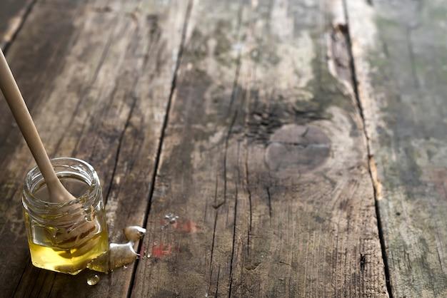 Miel bio en pot avec une baguette en bois sur un vieux fond en bois