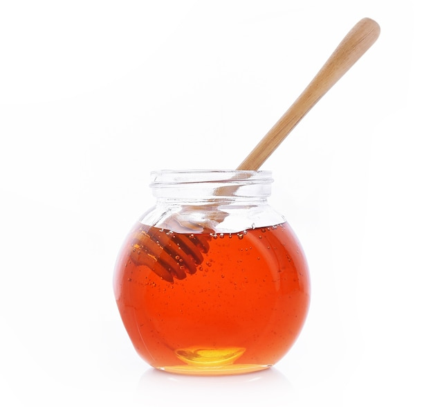 Miel de bouteille, cuillère sur le fond blanc