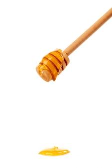 Miel avec un bruine en bois isolé sur fond blanc