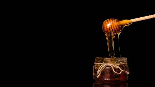 Le miel coule d'une cuillère dans un pot sur un fond noir.
