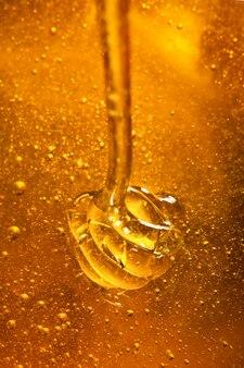 Le miel avec la couleur d'or coule d'une cuillère
