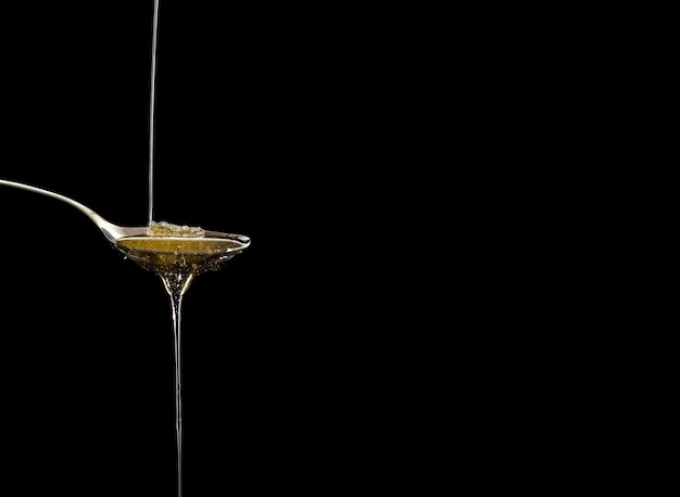 Miel cru organique sur la cuillère avec des gouttes de miel, pure douceur naturelle