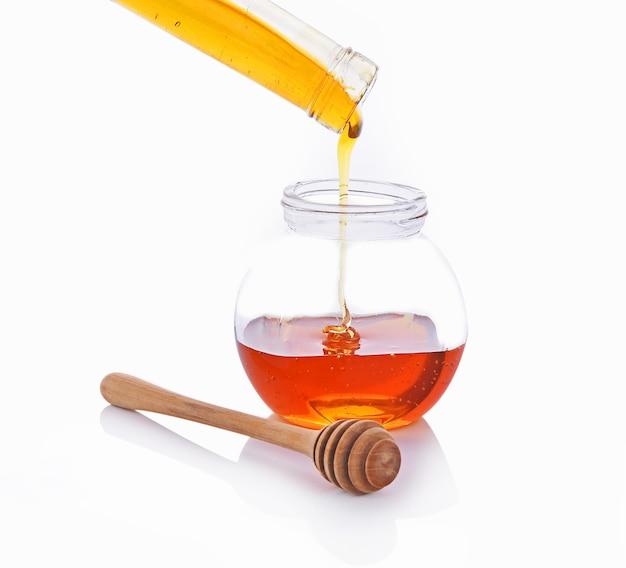 Miel de cuillère en bois, pot de miel sur le fond blanc