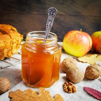 Miel dans un bocal en verre, noix et pommes