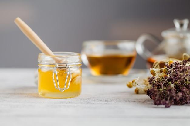 Miel dans un bocal en verre et tisane. miel et thé. flou artistique