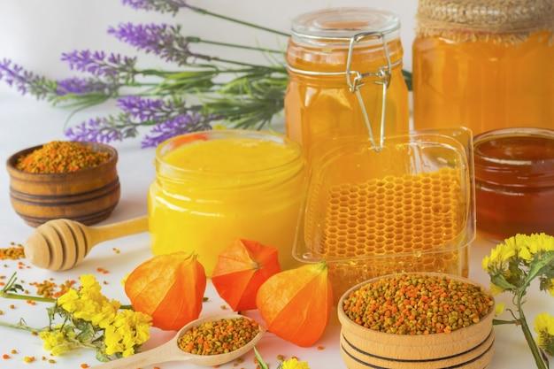 Miel dans des bocaux en verre. nids d'abeilles et pollen. fleurs
