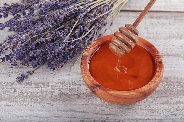 Miel dans un bol en bois avec une louche de miel et des fleurs de lavande sur fond de bois vintage blanc