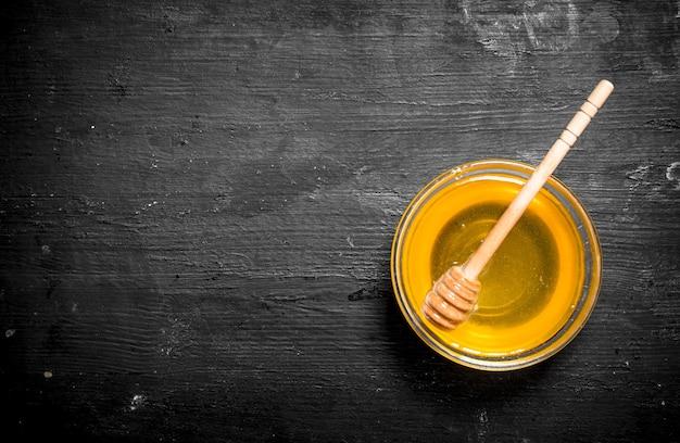 Miel dans un bol avec une cuillère. sur un tableau noir.