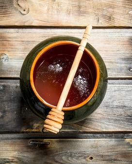 Miel dans une casserole avec une cuillère. sur un fond en bois.