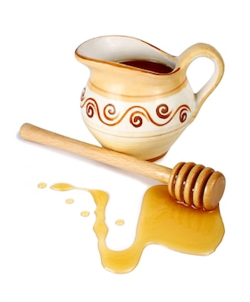 Miel dans une cruche et un bâton en bois