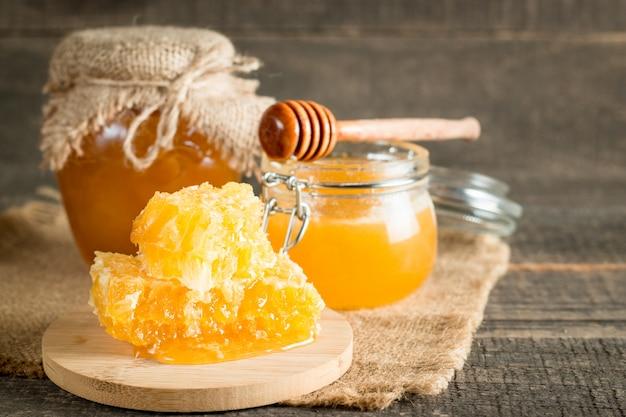 Miel dans un pot sur fond rustique en bois