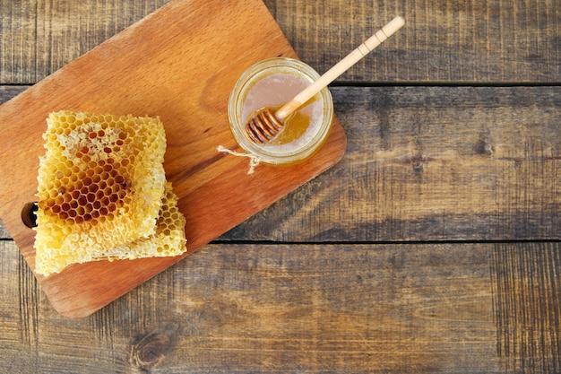Miel dans un pot et nid d'abeilles sur un vieux fond en bois. vue de dessus.