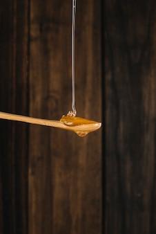 Miel dégoulinant sur une cuillère en bois