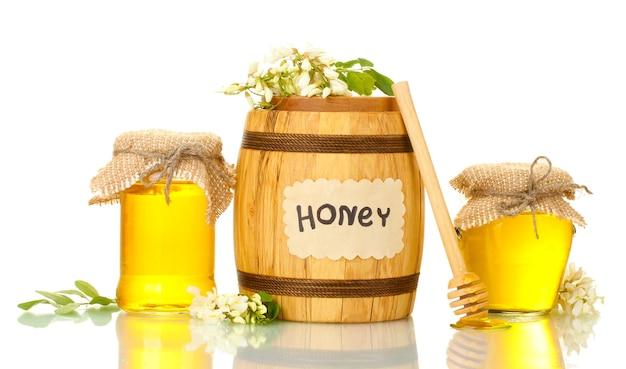 Miel doux en baril et bocaux avec des fleurs d'acacia sur blanc