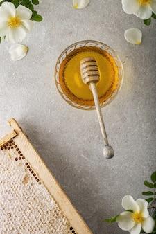 Miel doux dans le peigne, bocal en verre et une cuillère à miel sur la table. mur léger.