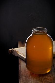 Miel doux frais dans un grand bocal en verre sur une table en bois