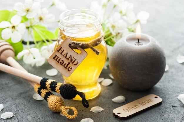 Miel avec des fleurs et une cuillère en bois