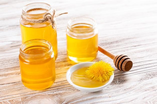 Miel de fleurs dans un bocal en verre et pissenlits sur une table en bois