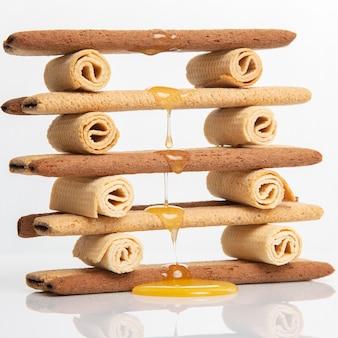 Le miel de fleurs fraîches coule et s'égoutte sur des bâtonnets de biscuits croustillants herdry. goûter de desserts.
