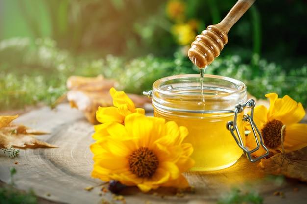 Miel de fleurs fraîches sur une table en bois. mise au point sélective.