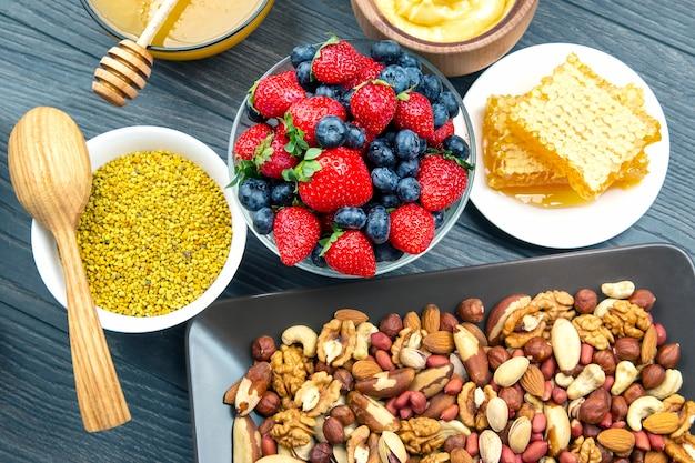 Miel frais assortis, noix, fraises et myrtilles sur un fond en bois. aliments sains en vitamines biologiques.