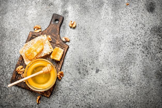Miel frais aux noix. sur fond rustique.