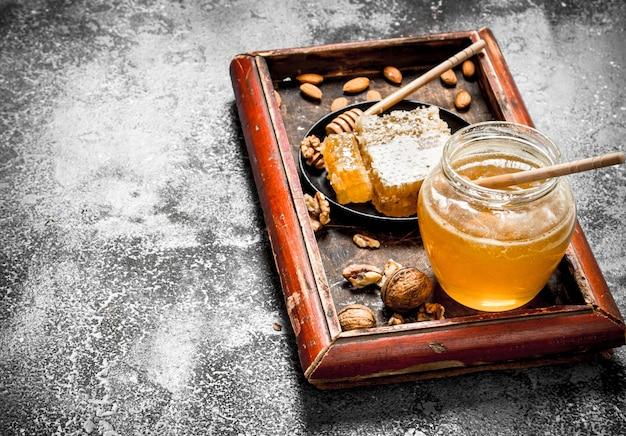 Miel frais aux noix. sur table rustique.
