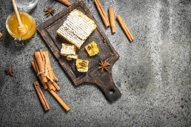 Miel frais avec des bâtons de cannelle. sur fond rustique.