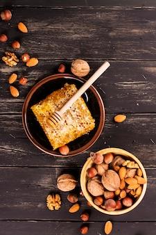 Miel frais dans le peigne et assortiment de noix sur un plateau métallique noir.