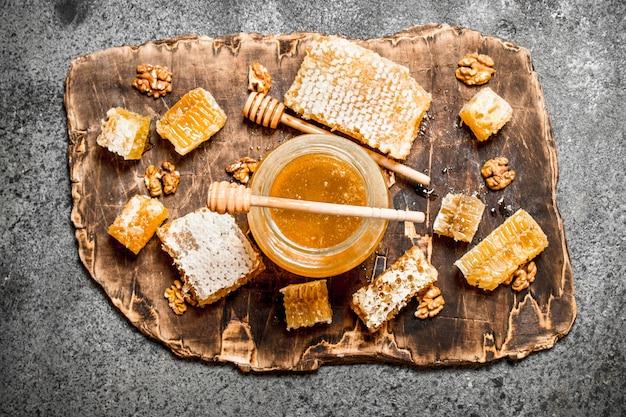 Miel frais dans un pot et nid d'abeille avec des noix sur table rustique.