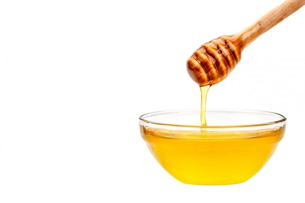 Miel frais dégoulinant d'une cuillère. sur un fond blanc