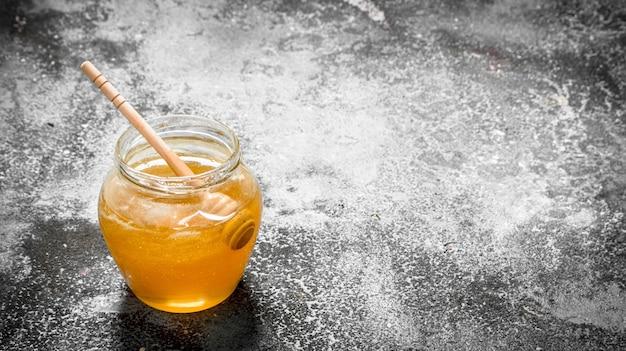 Miel frais en pot avec cuillère en bois. sur fond rustique.
