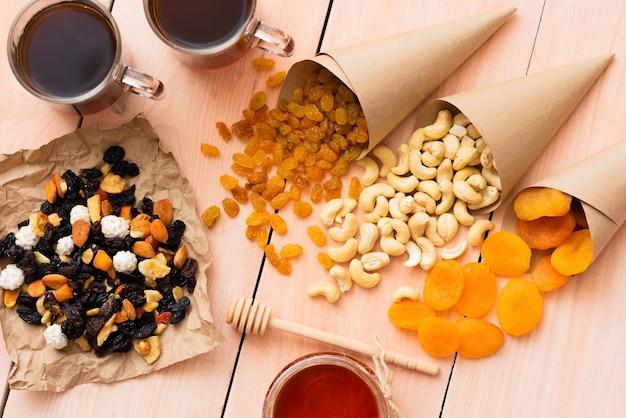 Miel et fruits secs sur une table en bois.