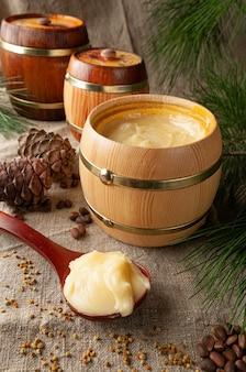 Miel en fûts de bois. sur fond de lin gris. décoré avec du pollen végétal, des aiguilles de pin, des noix et des cônes.