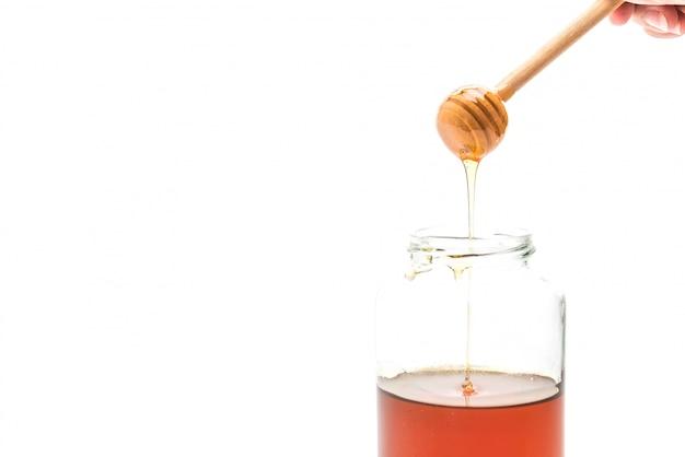 Miel goutte à goutte dans le pot