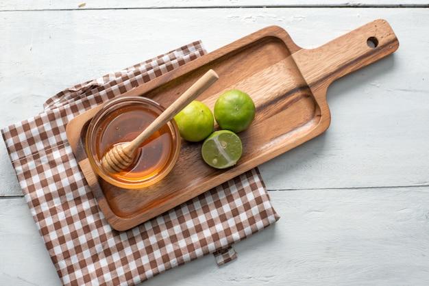 Miel avec une louche en bois de miel et de citron sur la table en bois