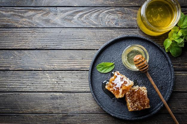 Miel avec louche de miel en bois et nid d'abeille sur table en bois foncé