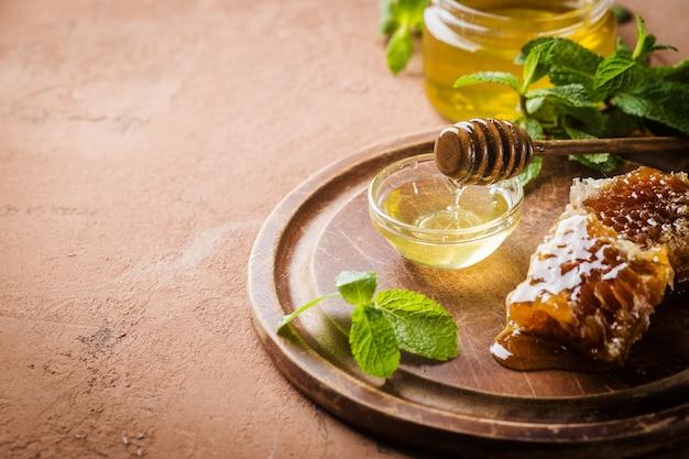 Miel avec louche de miel en bois et nid d'abeille sur table en pierre brune