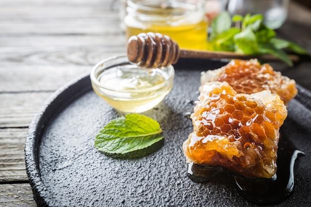 Miel avec louche de miel en bois et nid d'abeilles sur table en bois foncé