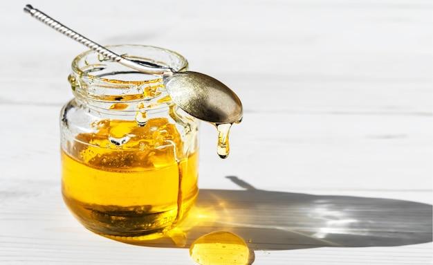 Miel naturel biologique dans un bocal en verre sur une surface en bois blanc