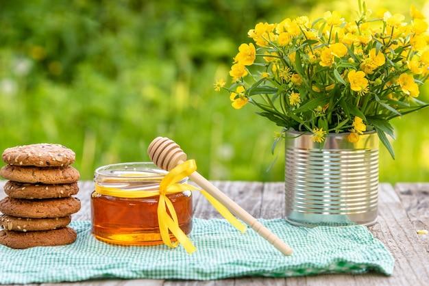 Miel naturel et biscuits avec un bouquet de fleurs dans la nature