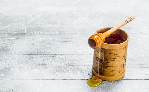 Miel naturel avec une cuillère. sur une surface rustique.