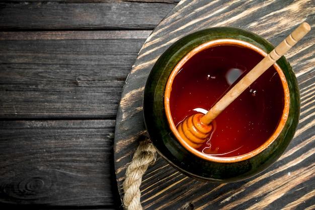 Miel naturel dans le pot sur une table en bois.