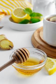 Miel naturel doré automne hiver boisson chaude ingrédient bol en verre cuillère à miel saisonnier