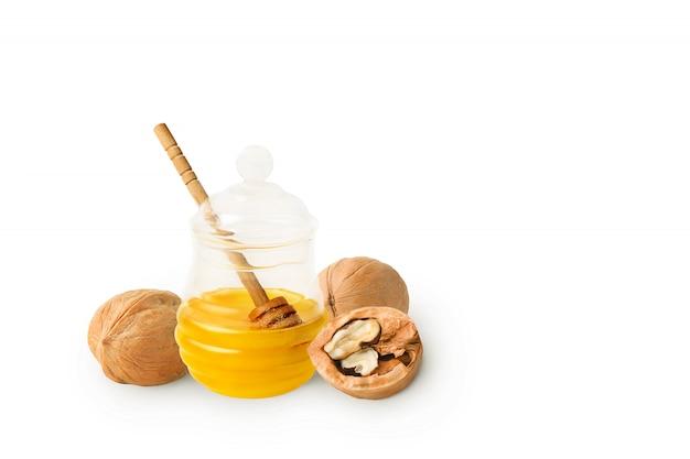Miel naturel fait maison dans un bocal en verre avec une louche aux noix. isolé.