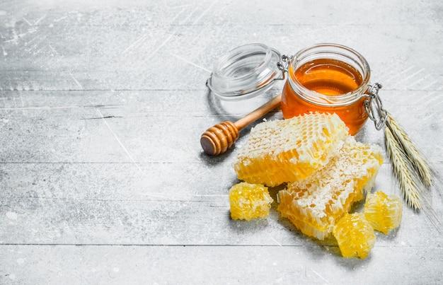 Miel naturel en nids d'abeilles. sur une surface rustique.