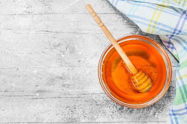 Miel naturel en pot avec cuillère en bois. sur une surface rustique.